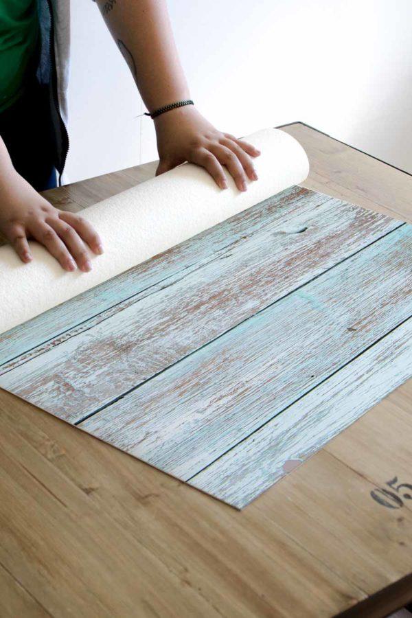 alfombra_enrollada_madera_blanca