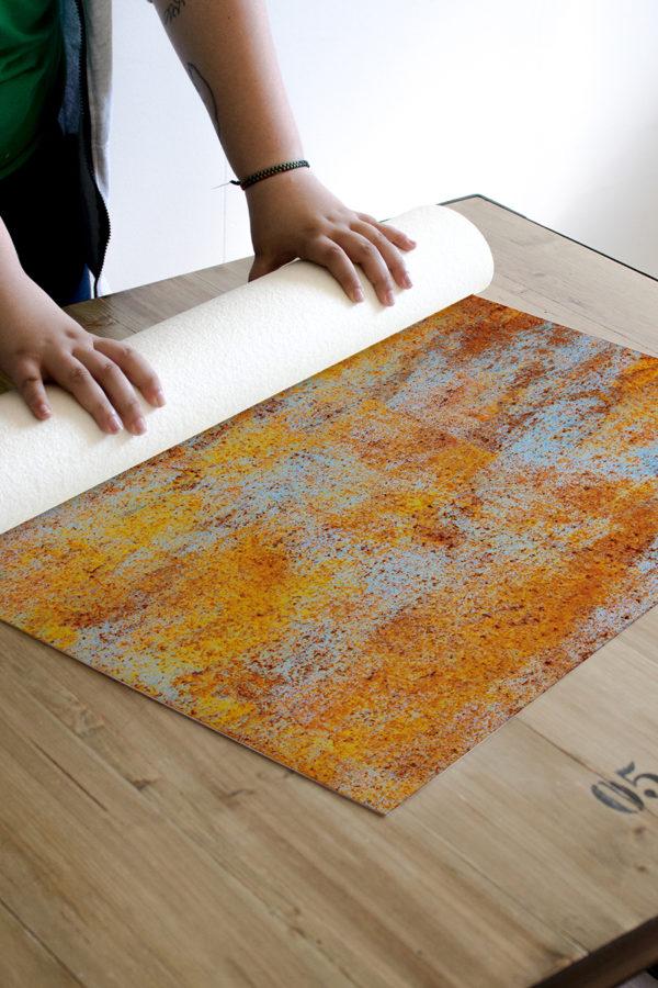 Alfombra vinílica Óxido en tonos naranjas y detalles en azul claro.