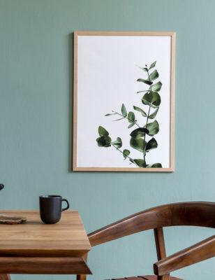 Lámina Rama con Hojas con marco de madera sobre pared verde menta.